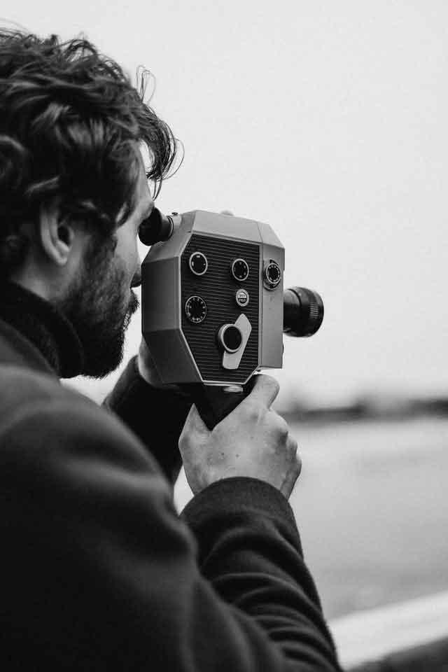 Hombre con camara anitgua filmando